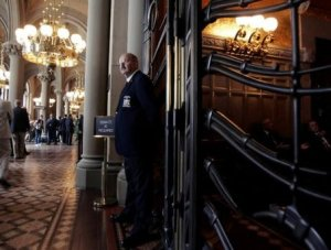 Associated Press A sergeant at arms staff member stands in front of a locked gate leading to the state Senate Chamber at the Capitol in Albany, Wednesday.